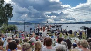 Dirigent Nille klar med prosjektkoret foran Skibldner, Atlungstad brygge. Foto: S.J. Langsjøvold